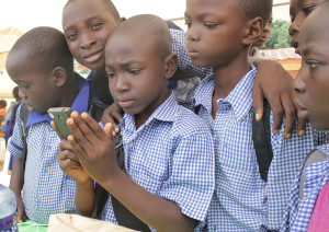 Kids in Nigeria gather around to look at the Sesame Square content now on available on Worldreader Mobile.