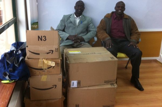 Shadrack Lemiso, an educator and partner, smiles at boxes of e-readers en route to the Kilgoris Project in Kenya.