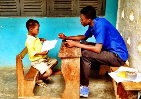 Robert (right), a Worldreader volunteer, conducts a reading assessment with a first-grade student.