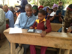 Students at Nganana Schools show their parents how much they like their e-readers