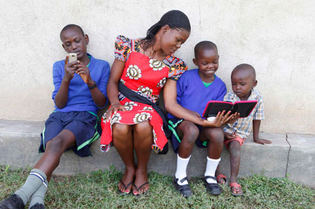 Mother reading to her kids on an e-reader and teenager on a mobile phone.
