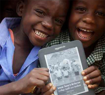 Worldreader students hold a Kindle with the cover of Where There is No Doctor displayed on the screen