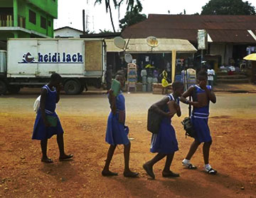 Students carrying Worldreader Kindles walk to school