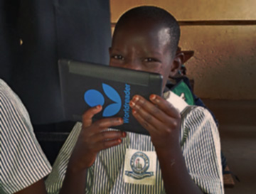 HUMBLE student Benetta in Uganda covers a smile with her new Kindle