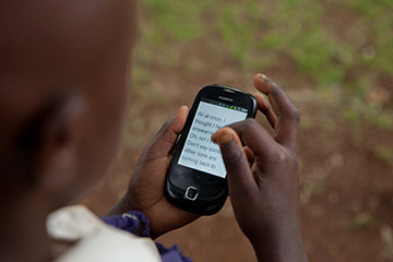 A girl reads on her feature phone using Worldreader Mobile