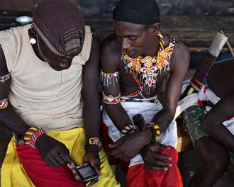 Kenyans read from a mobile phone. (Photo by Siegfried Modola for Reuters)