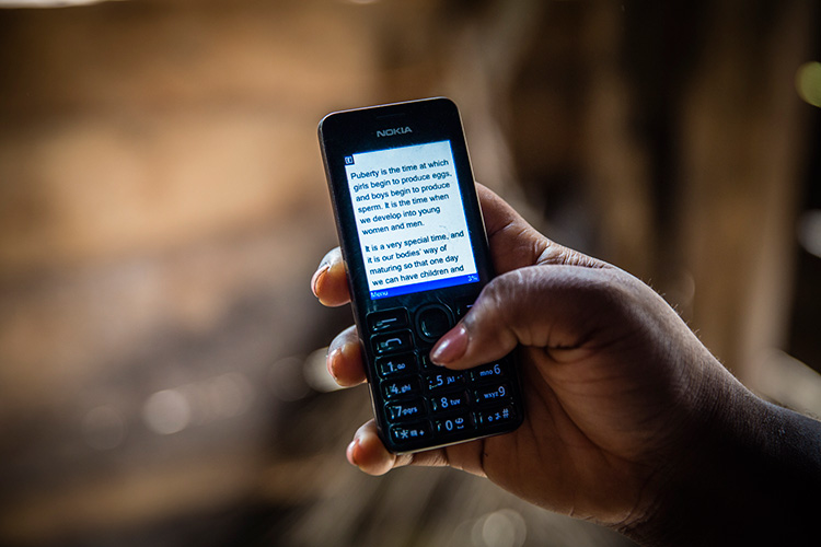 Woman reading about sexual health on worldreader mobile on her mobile phone