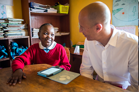 David Risher reads with a student in a Worldreader school program in Africa