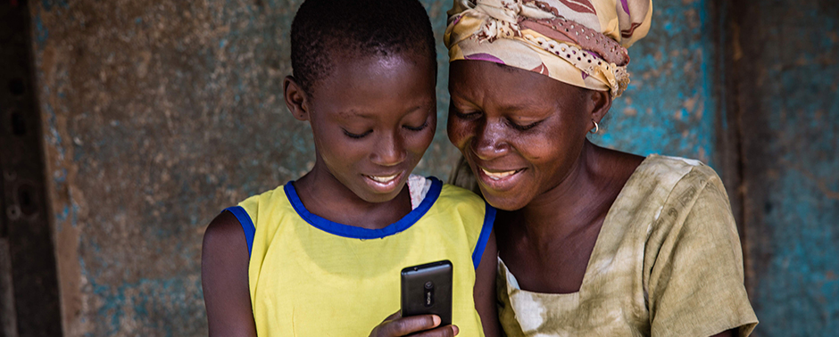 Two women read books from the Worldreader library on a Kindle