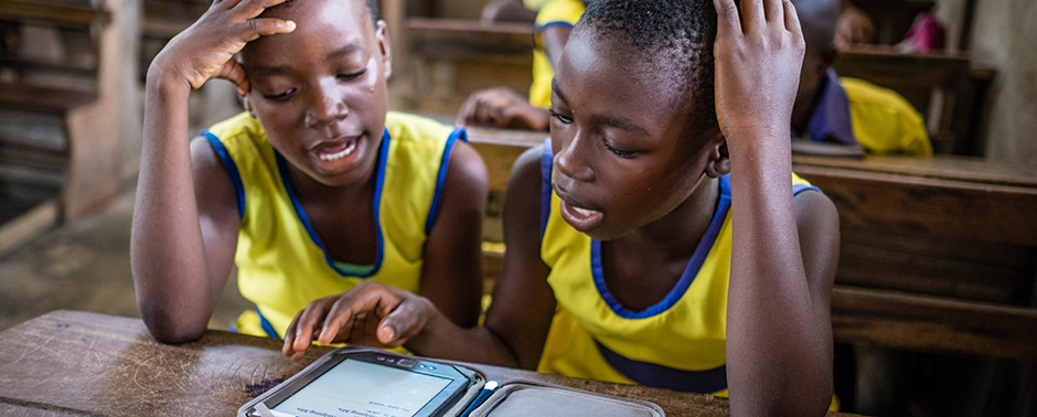 Students reading from a Worldreader e-reader in school